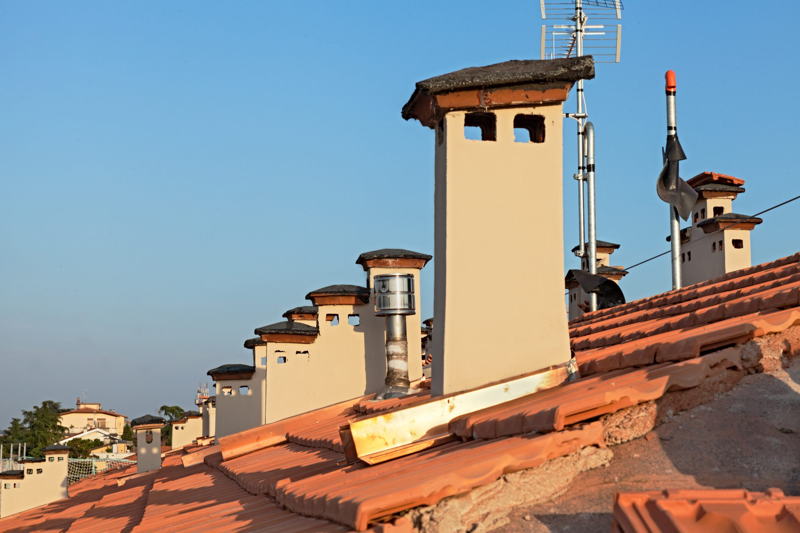 row of chimneys on the rooftop of a building - roof renovation: installation of new tiles and chimney
